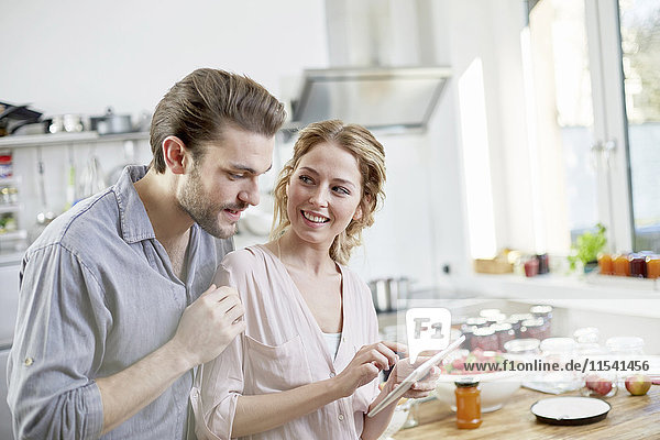 Paar betrachtet digitales Tablett in der Küche