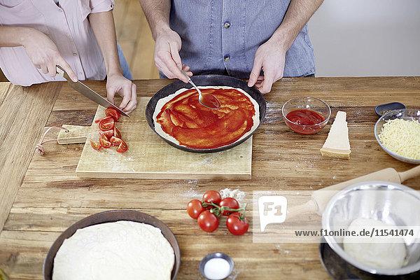 Paar Zubereitung der Pizza in der Küche