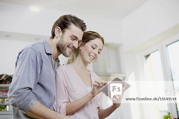 Lächelndes Paar schaut auf digitales Tablett in der Küche