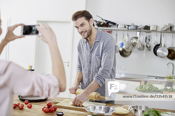 Frau macht Handyfoto von lächelndem Mann bei der Teigzubereitung in der Küche