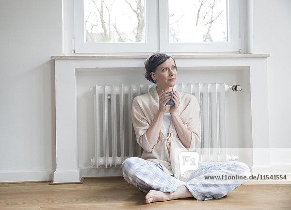 Frau zu Hause auf dem Boden sitzend  Tasse haltend