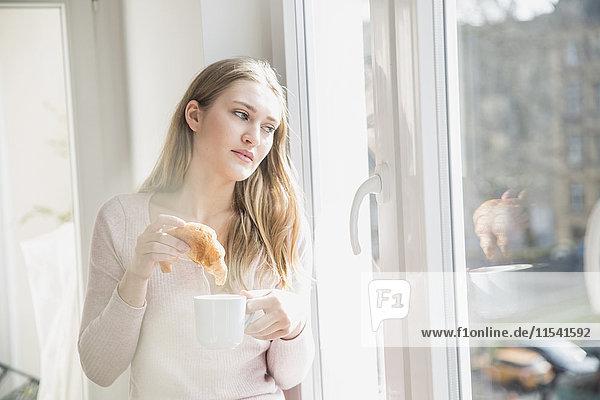 Porträt der jungen Frau mit Croissant und Tasse Kaffee durchs Fenster schauend