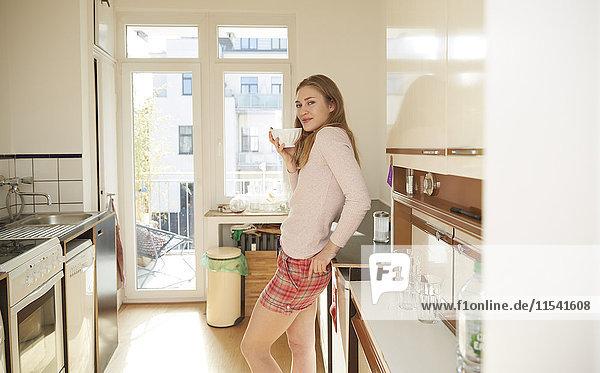 Lächelnde junge Frau stehend in der Küche mit einer Schüssel Kaffee