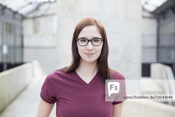Porträt einer lächelnden jungen Frau mit Brille