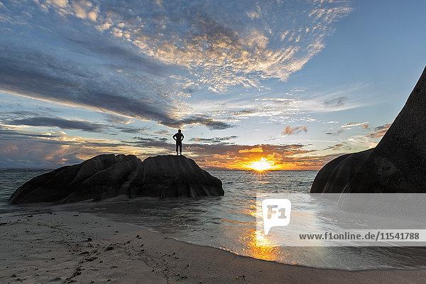 Seychellen  La Digue  Strand  Mann steht auf Granitfelsen bei Sonnenuntergang
