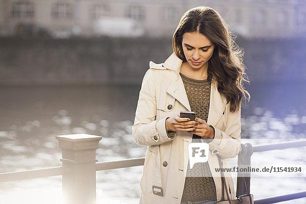 Deutschland  Berlin  junge Frau mit Smartphone an der Spree