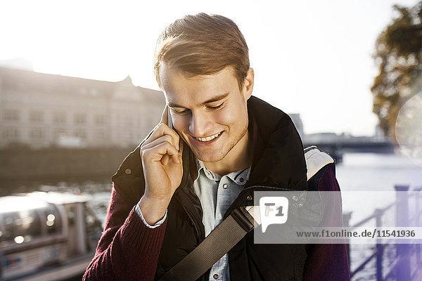 Deutschland  Berlin  junger Mann am Telefon an der Spree