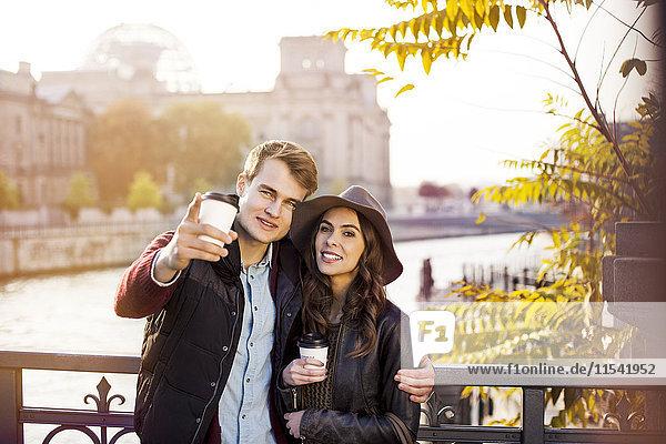 Deutschland  Berlin  junges Paar an der Spree mit Kaffee zum Mitnehmen