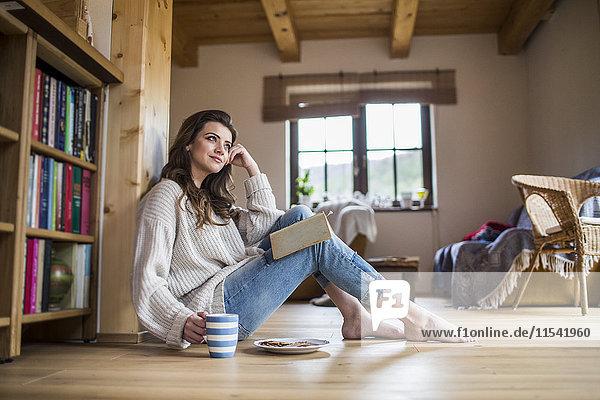 Junge Frau zu Hause beim Lesen eines Buches