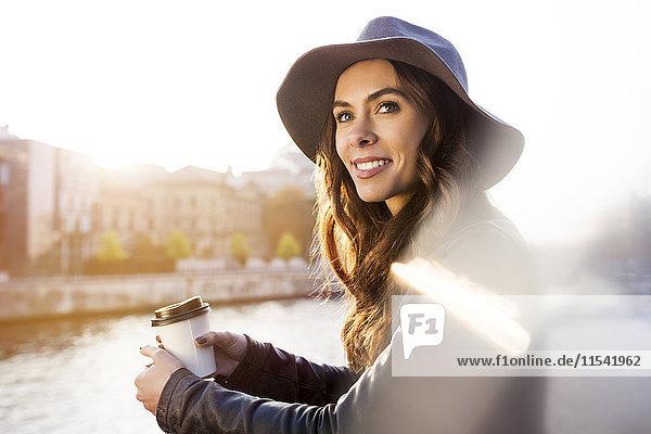 Deutschland  Berlin  junge Frau mit Kaffee an der Spree