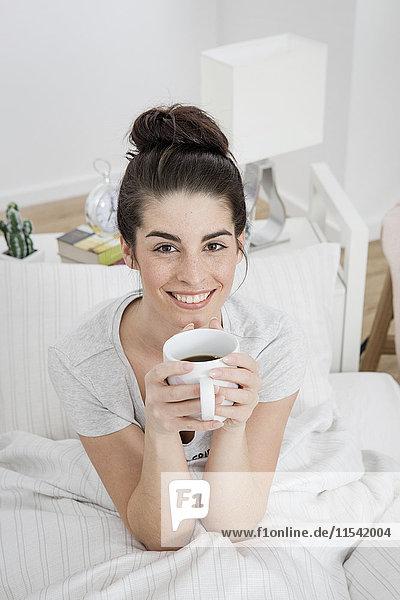 Porträt einer lächelnden jungen Frau mit einer Tasse Kaffee im Bett