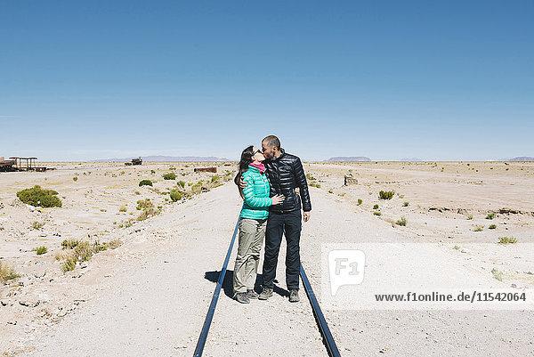 Bolivien  Uyuni-Zugfriedhof  Pärchen küssen sich auf der Eisenbahn