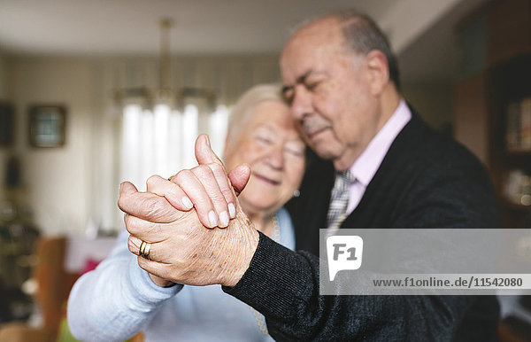 Hands of senior couple dancing together at home
