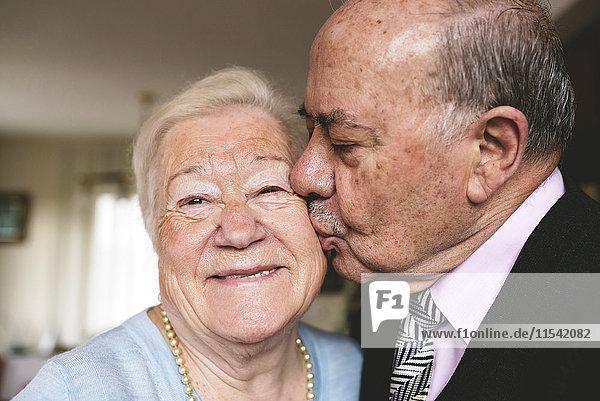 Ein älterer Mann küsst seine glückliche Frau.