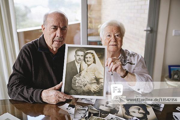 Seniorenpaar zeigt ihr Hochzeitsfoto zu Hause