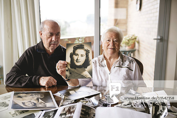 Senior woman showing an old picture of herself