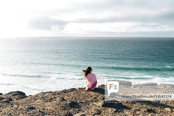Spanien  Fuerteventura  El Cotillo  Rückansicht der Frau mit Blick aufs Meer