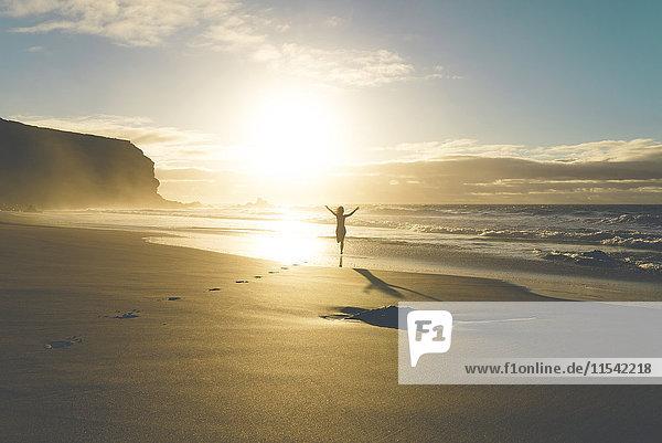 Frau am Strand  die bei Sonnenuntergang zum Wasser rennt.