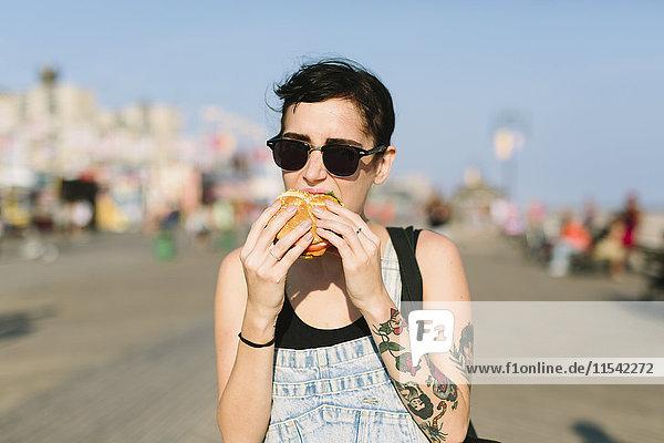 USA  New York  Coney Island  junge Frau beim Hamburgeressen
