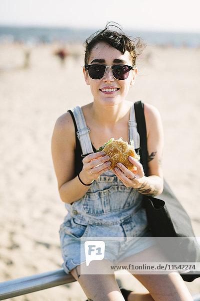 USA  New York  Coney Island  junge Frau beim Hamburgeressen am Strand