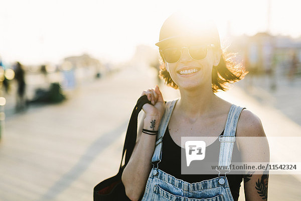 USA  New York  Coney Island  lächelnde junge Frau an der Strandpromenade bei Sonnenuntergang