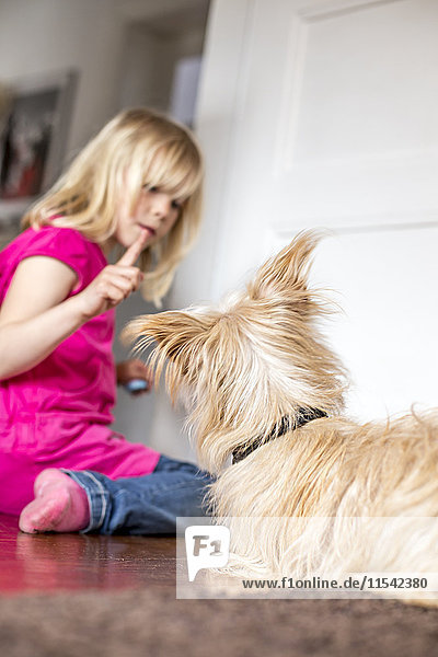 Little girl with her dog at home
