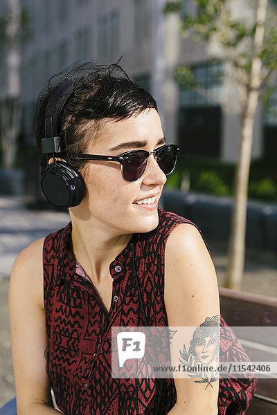 Portrait der tätowierten jungen Frau mit Kopfhörer und Sonnenbrille