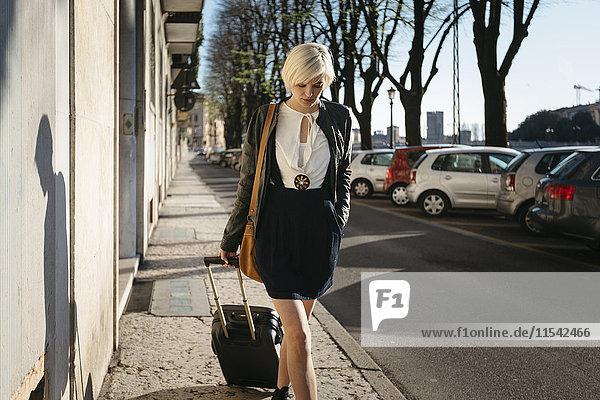 Italien  Verona  blonde Frau mit Gepäck auf dem Gehsteig