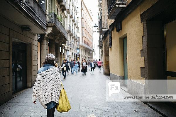 Spanien  Barcelona  junge Frau  die in einer Gasse läuft