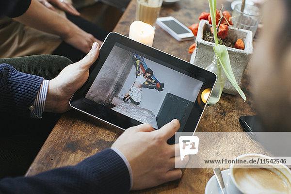 Mann in einem Café mit Bild auf digitalem Tablett für Freunde