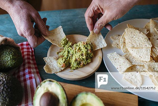 Hände greifen Nachos mit Guacamole