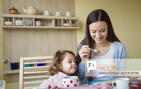 Mutter und ihre kleine Tochter zusammen am Frühstückstisch