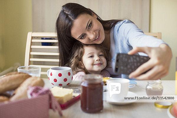 Porträt der Mutter und ihrer kleinen Tochter,  die einen Selfie am Frühstückstisch nehmen