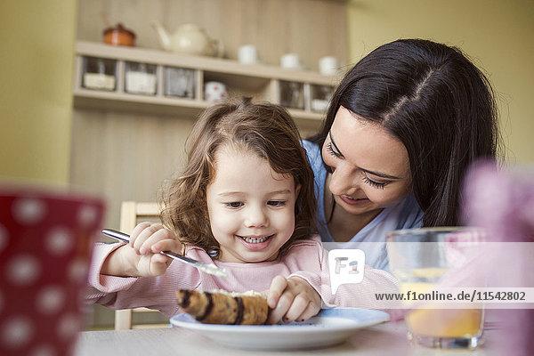 Porträt des kleinen Mädchens und ihrer Mutter am Frühstückstisch