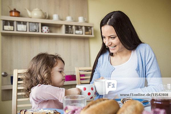 Mutter und ihre kleine Tochter stoßen mit ihren Tassen am Frühstückstisch an.