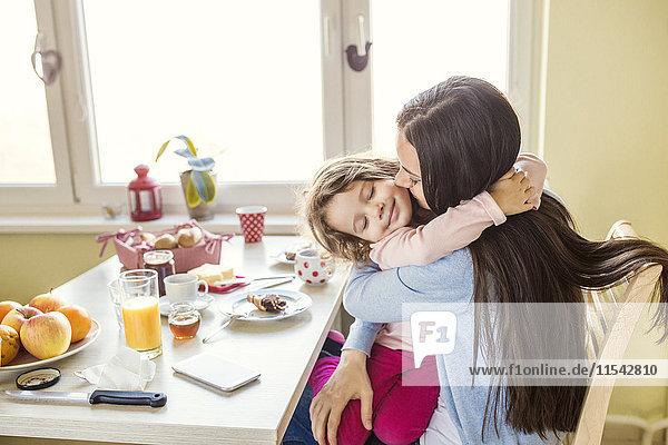 Porträt eines lächelnden kleinen Mädchens  das seine Mutter am Frühstückstisch umarmt.