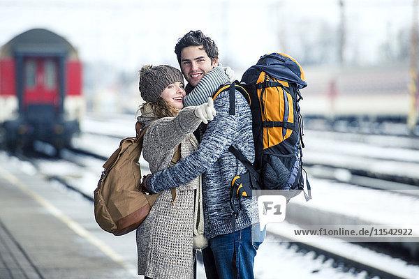 Lächelndes junges Paar umarmt auf dem Bahnsteig