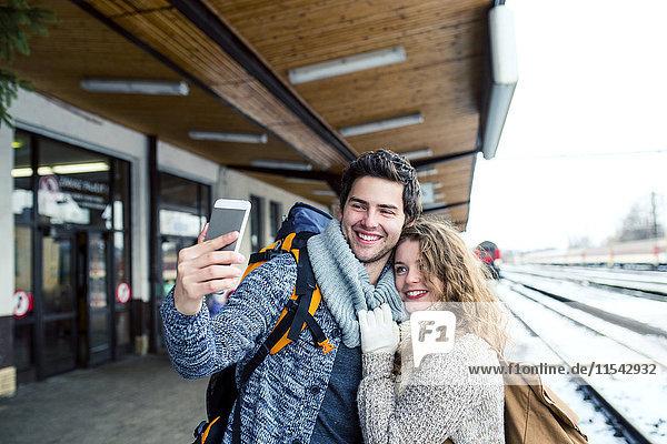 Glückliches junges Paar auf dem Bahnsteig mit einem Selfie
