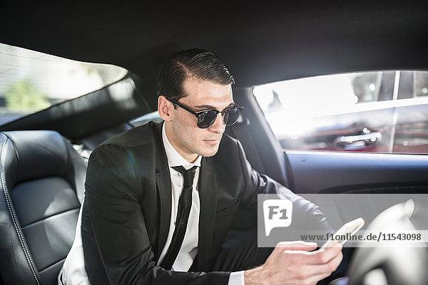Geschäftsmann im Auto mit Handy