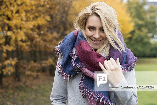Porträt einer fröhlichen jungen Frau mit modischem Schal im herbstlichen Park