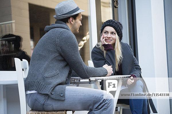 Verliebtes Paar hält sich an den Händen im Straßencafé