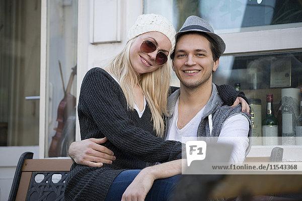 Porträt eines verliebten Paares auf einer Bank sitzend