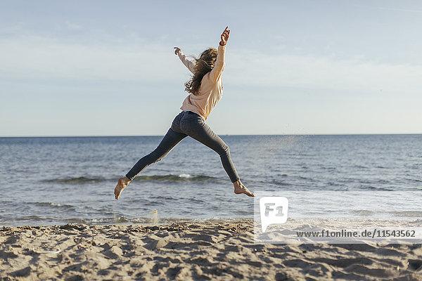 Spanien  Lleida  Frau beim Springen am Strand