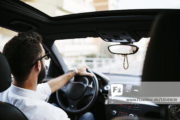 Junger Mann beim Autofahren