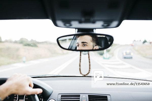 Junger Mann beim Autofahren  Nahaufnahme des Rückspiegels