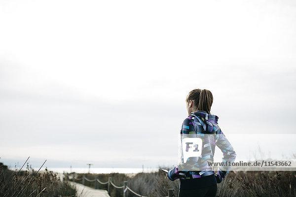 Spanien  Tarragona  Frau bereit zum Laufen auf einem Holzsteg