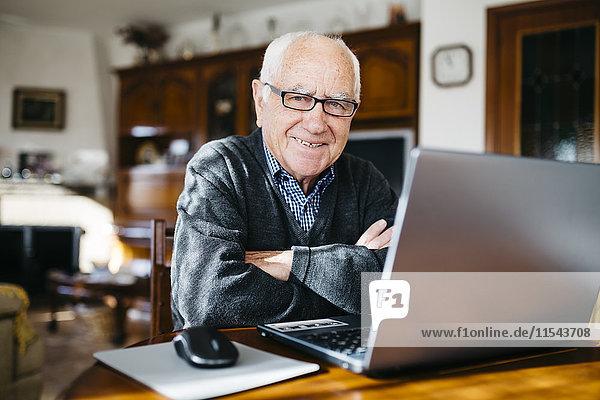 Porträt eines lächelnden älteren Mannes mit Laptop zu Hause