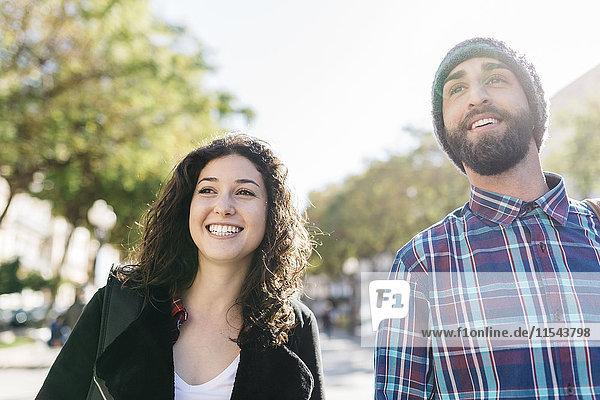 Lächelndes junges Paar im Freien  das sich umsieht.