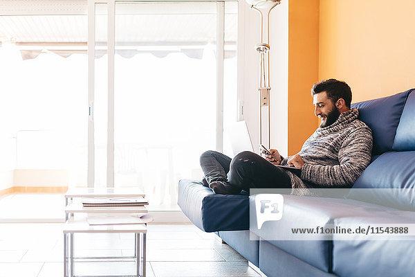 Bartiger junger Mann  der zu Hause entspannt auf der Couch sitzt  mit Laptop und Handy.