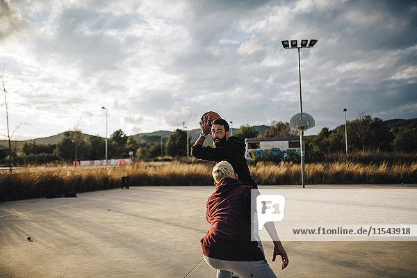 Zwei junge Männer beim Basketballspielen auf einem Außenplatz